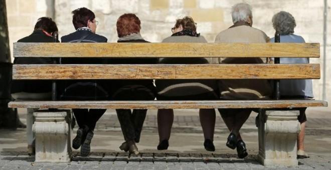 Varios pensionistas sentados en un banco en la localidad burgalesa de Briviesca. AFP