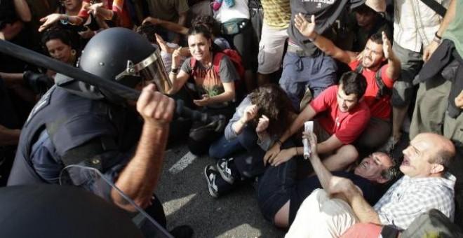 Varios agentes de Policía participan en el desalojo de la acampada de la plaza de Catalunya. REUTERS