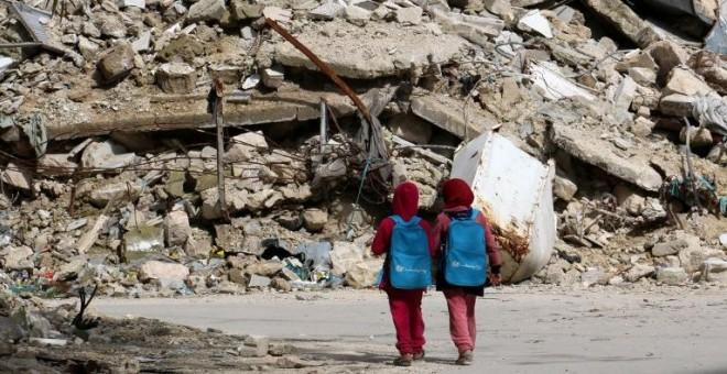 Dos niñas con mochilas donadas por UNICEF pasan junto a un edificio derruido en Alepo de camino a la escuela. Fotografía de marzo de 2015. - ZEIN AL-RIFAI (AFP)