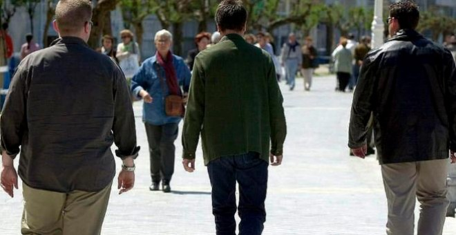Escoltas de espaldas acompañan a un político. /EFE