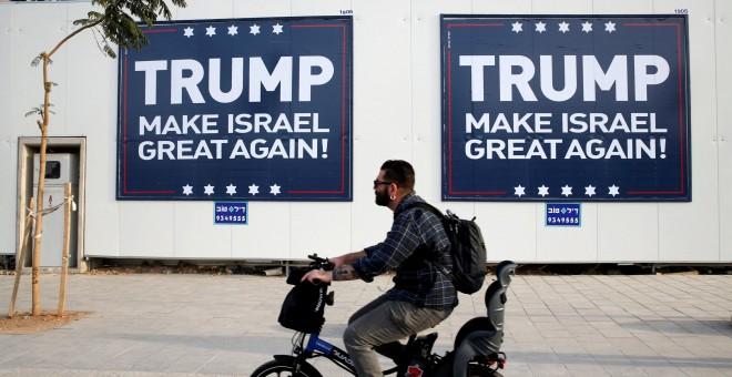 Un hombre montado en bicicleta pasa junto a unos letreros en Tel Aviv parafraseando el lema de campala de Donadl Trump. REUTERS/Baz Ratner