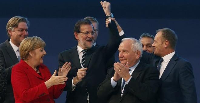 El presidente del Consejo Europeo, Donald Tusk (dcha.), levanta el brazo de Rajoy, junto al presidente el PPE, Joseph Daul (2dcha.), y Angela Merkel. EFE