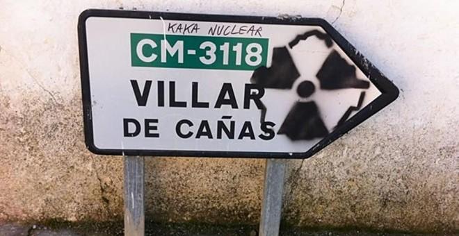 Una pintada contra el cementerio nuclear en un indicador de carrera de Villar de Cañas. EFE