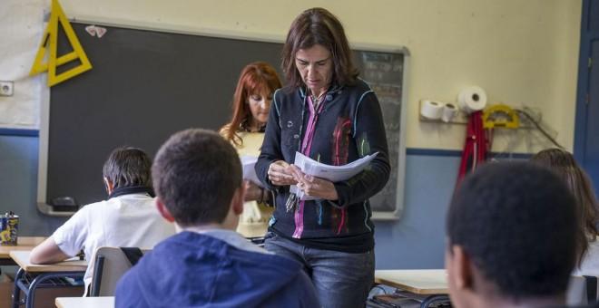 Una profesora reparte exámenes en un aula. EFE