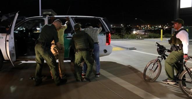 Agentes de la patrulla de frontera de EEUU detienen a unoshombres de la India que han entrado en el país saltando sobre la valla con México, cerca de la localidad de Calexico, en el Estado de California. REUTERS/Mike Blake