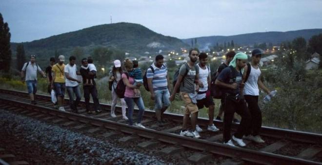 Inmigrantes caminan por las vías hacia la frontera de Austria. EFE/Balasz Mohai
