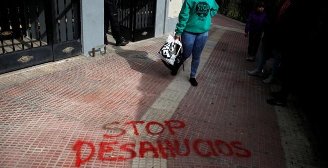 Una mujer abandona su domicilio en la localidad madrileña de Parla después de haber sido sesahuciada. REUTERS/Juan Medina