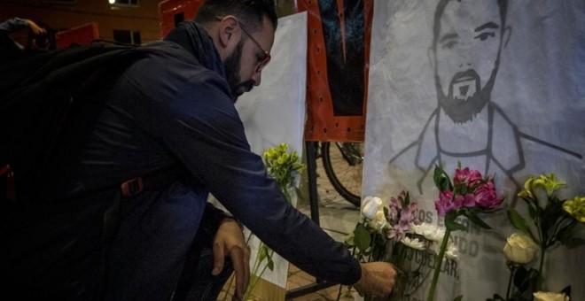 Un hombre coloca flores durante una vigilia en Bogotá, en homenaje a los líderes sociales asesinados en Colombia.- MARCHA PATRIÓTICA