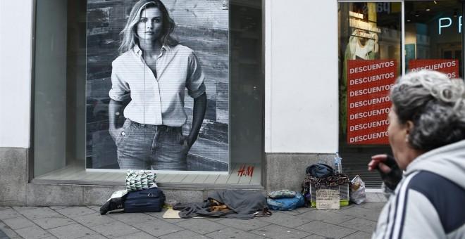 Enseres personales de una persona sintecho junto a dos grandes tiendas de ropa. EUROPA PRESS