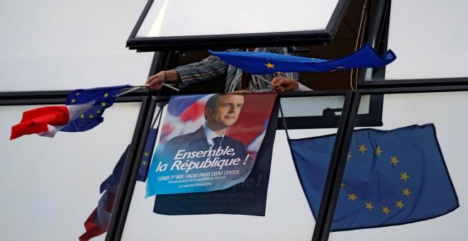 Uno de los carteles de campaña de Emmanuel Macron rodeado de banderas de la Unión Europea.- REUTERS