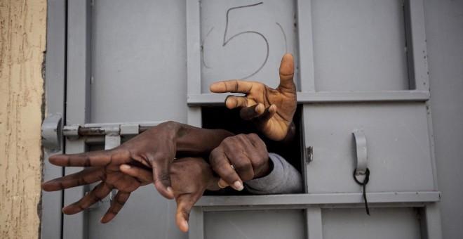 Siete migrantes subsaharianos sacan las manos por la ventana de una celdaen el Centro de Detención de Garabuli, suplicando agua, cigarros, comida y su liberación /Narciso Contreras