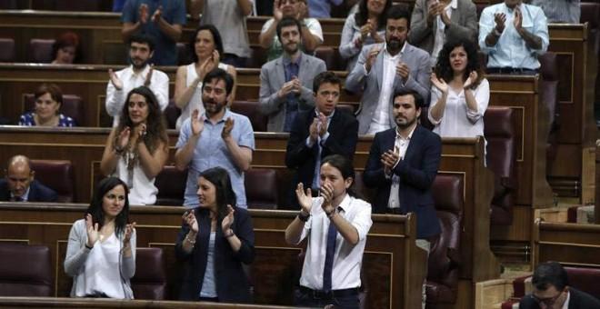 Los diputados de Podemos aplauden a uno de los suyos. | EFE