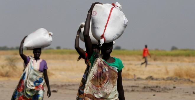 Varias mujeres llevan sacos de alimentos en el pueblo Nimini, en el estado de Unity, al norte de Sudán del Sur.- REUTERS / Siegfried Modola