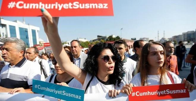 Varias presonas muestran el lema 'Cumhuriyet no se silencia' durante una concentración delante del Palacio de Justicia de Estambul (Turquía) hoy, 24 de julio de 2017. Empleados del diario se sientan en el banquillo de los acusados hoy acusados de colabora