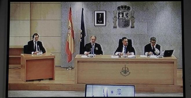 Imagen del monitor de la sala de prensa de la Audiencia Nacional de San Fernando de Henares del presidente del Gobierno, Mariano Rajoy (i). /EFE