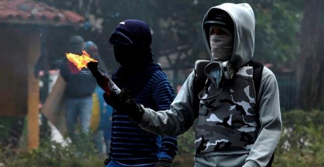 Manifestantes opositores se enfrentan a agentes de la Guardia Nacional Bolivariana mientras bloquean una calle en rechazo a las elecciones de la Asamblea Nacional Constituyente, en Barquisimeto. EFE/Pascuale Giorgio