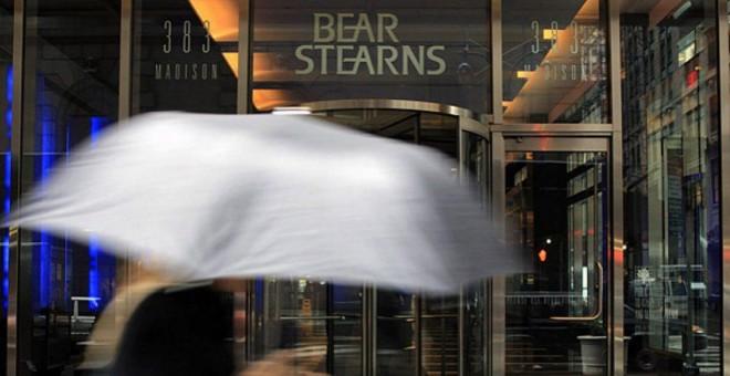 Una mujer con paraguas pasa junto a la entrada a la sede de Bear Stearns en Nueva York. AFP