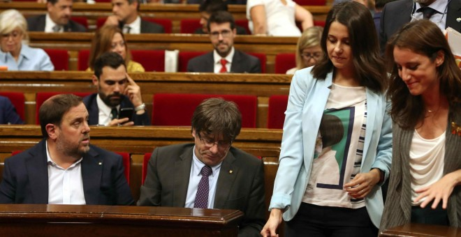 Las diputadas Inés Arrimadas, de Ciudadanos, y Andrea Levy, del PP, pasan junto a los escaños del president de la Generalitat, Carles Puigdemont, y del vicpresidente, Oriol Junqueras, en Parlament de Catalunya. EFE/Toni Albir