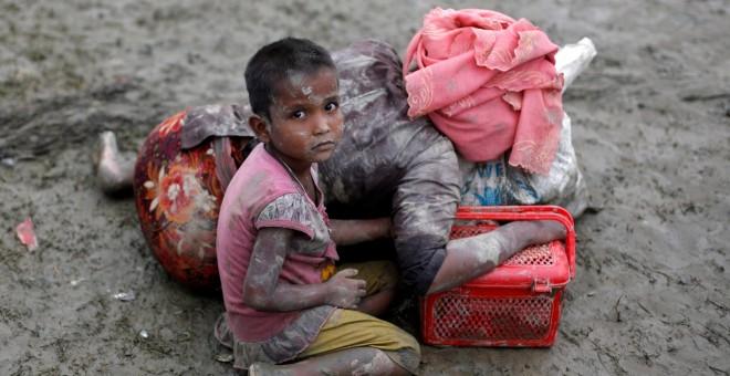 Una niña ronhinyá sentada junto a su madre, que descansa tras cruzar la frontera entre Brimania y Bangladesh. - REUTERS