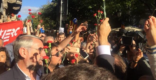 Concentració de protesta davant el Departament d'Economia i Hisenda de la Generalitat. Reparteixen clavells per donar als policies