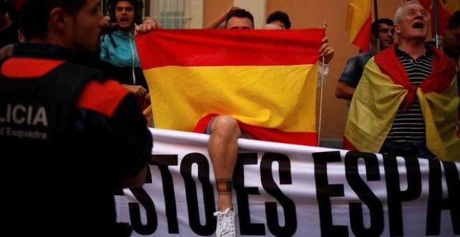 Manifestantes sostienen banderas españolas durante una reunión en apoyo a los guardias civiles españoles fuera de sus cuarteles en Barcelona el pasado 21 de septiembre / REUTERS