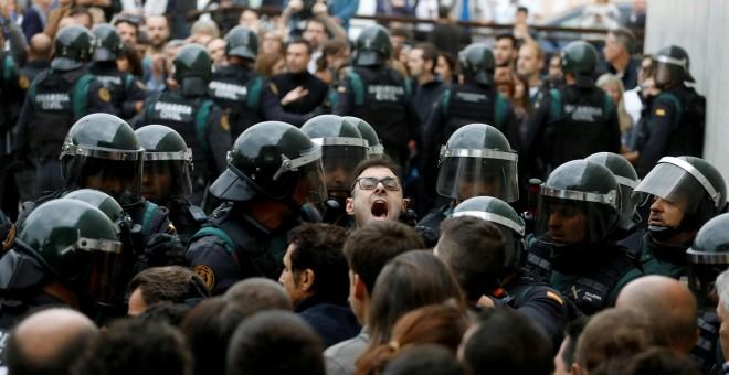 Agentes de la Guardia Civil tratan de cerrar el colegio electoral de Sant Julia de Ramis (Girona), donde tenía que havber votado el presiodent de la Generalitat, Carles Puigdemont. REUTERS / Juan Medina