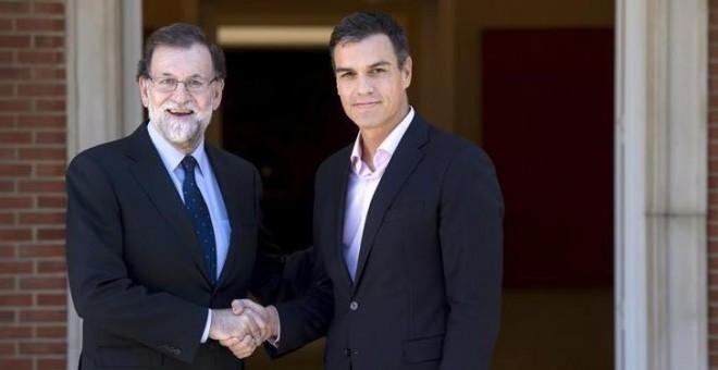 Rajoy y Sánchez se saludan en la escalinata de la Moncloa. | EFE