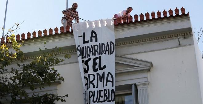 Empleados de la embajada española en Atenas retiran la pancarta 'La solidaridad es el arma del pueblo'. /REUTERS