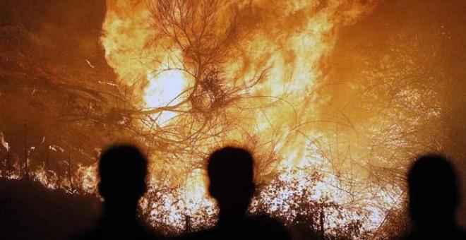 Varias personas observan un incendio en Chandebrito. | LAVANDEIRA JR. (EFE)