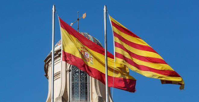 Las banderas de España y de Catalunya siguen ondeando en el Palau de la Generalitat donde este viernes el Parlament proclamó la Declaración Unilateral de Independencia. REUTERS/Yves Herman