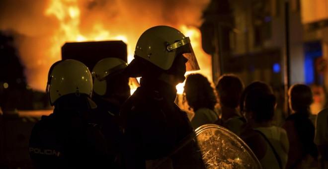 Imagen de un grupo de bomberos tras el incendio de varios contenedores de basura. EFE