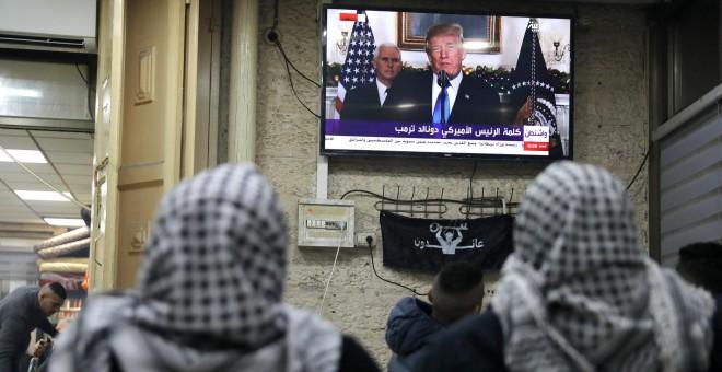 Palestinos escuchan el discurso de Trump en el que reconoce oficialmente a Jerusalén como capital de Israel. REUTERS/Ammar Awad