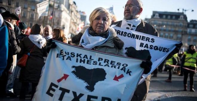 Una mujer sujeta una pancarta en París que pide la reagrupación de los presos de ETA.EFE/Julien de Rosa