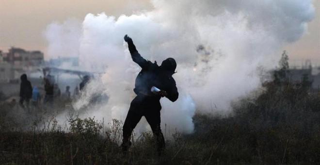 Un manifestante palestino devuelve una granada de gas israelí durante enfrentamientos cerca a la frontera con Israel. EFE/MOHAMMED SABER
