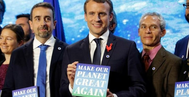 El presidente francés, Emmanuel Macron, en la cumbre One Planet Summit, con un cartel que dice 'Make our planet great again'.