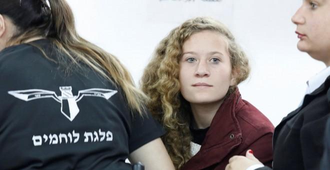 La adolescente palestina  Ahed Tamimi, es escoltada por agentes de la policía israelí hacia un juzgado en la localidad de Betunia (Palestina). EFE/ Abir Sultan