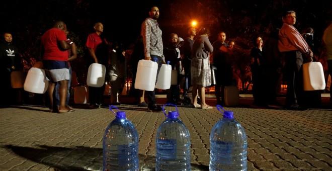 Varios ciudadanos hacen cola para recoger agua de una fuente en uno de los suburbios de Ciudad del Cabo. REUTERS