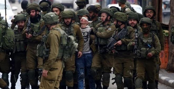 Soldados israelíes detienen a un joven palestino durante unas protestas contra la decisión del presidente estadounidense, Donald Trump, de reconocer a Jerusalén como capital de Israel, en la ciudad cisjordana de Hebrón (Palestina). Abed Al Hashlamoun (EFE