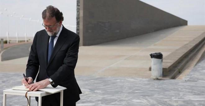 El presidente del Gobierno, Mariano Rajoy, firma en el libro de honor a las victimas de la dictadura argentina durante su visita al Parque de la Memoria. / EFE