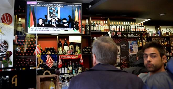 Varias personas en un bar en Bilabo miran la información en la televisión del anuncio del 'desmantelamiento total' de ETA. REUTERS/Vincent West