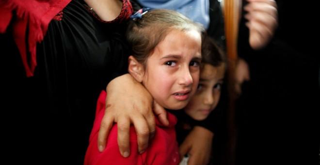 Familiares palestinos de Azam Ewidah, el chico de 15 años, asesinado en la frontera entre Israel y Gaza, lloran durante su funeral en el sur de la Franja de Gaza el 28 de abril de 2018.- REUTERS