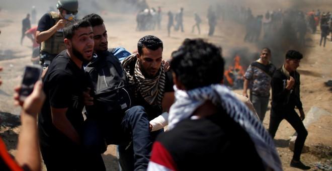Varios palestinos trasladan a un herido en las protestas en Gaza contra la embajada de EEUU en Jerusalén. - REUTERS