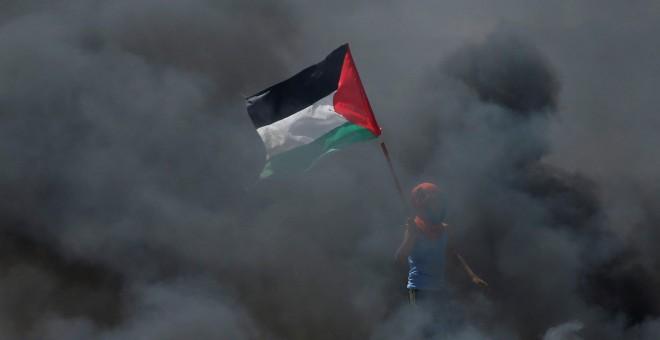 Un chico sostiene una bandera palestina en medio del humo durante las protestas contra el traslado de la embajada de EEUU a Jerusalén. / Reuters