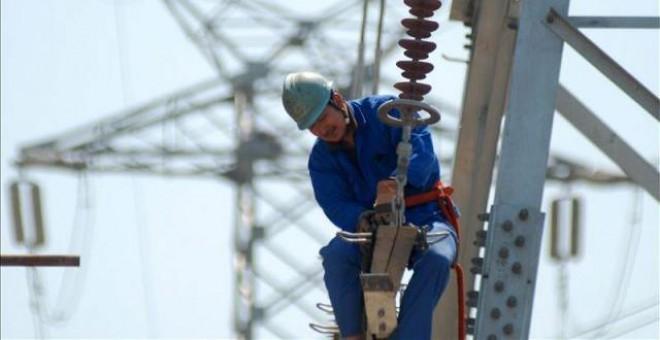 Un trabajador instala nuevas líneas de alto voltaje en una torre de electricidad. EFE/Archivo