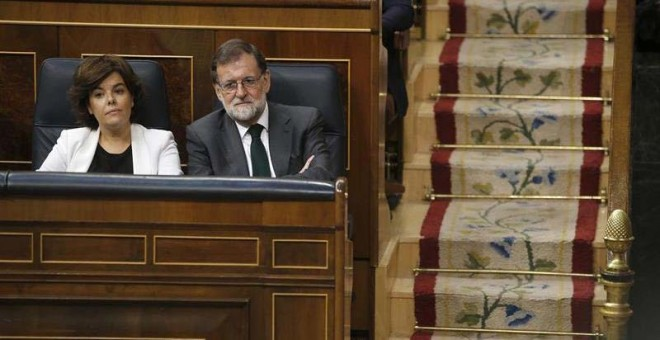 La vicepresidenta del Gobierno, Soraya Sáenz de Santamaría, y el presidente Mariano Rajoy siguen la votación. (EFE)