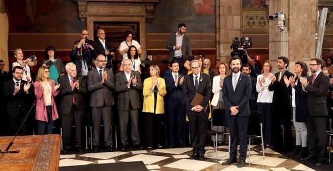 El presidente de la Generalitat, Quim Torra (i), y el del Parlament de Cataluña, Roger Torrent (d), reciben el aplauso de los nuevos consellers del gobierno catalán a su llegada al acto de toma de posesion del nuevo Govern que se celebra hoy en el Palau d