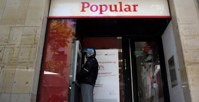 Un hombre saca dinero de un cajero automático del Banco Popular, en la localidad barcelonesa de Vilanova i la Geltru, en una foto del 7 de junio de 2017, el día que se anunció la resolución de la entidad. AFP/Lluis Gené