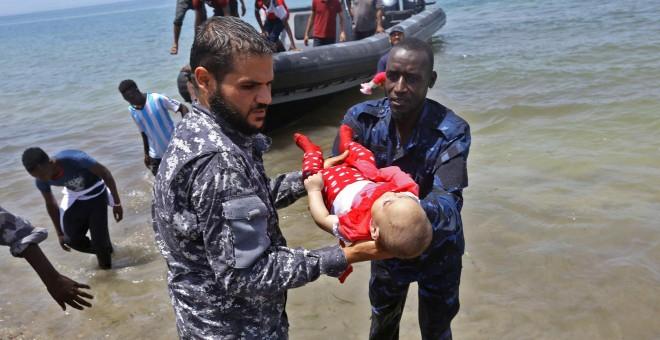Guardacostas libios sostienen los cadáveres de tres bebés fallecidos en el naufragio frente a las costas libias. Hay cien desaparecidos y 16 supervivientes.- AFP/ MAHMUD TURKIA