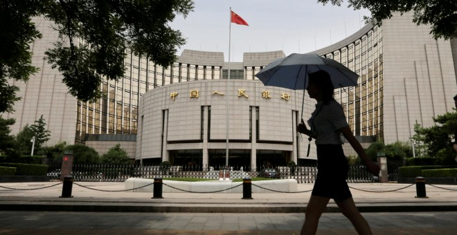 Una mujer camina frente al edificio del  People's Bank of China (PBOC) en Beijin./REUTERS