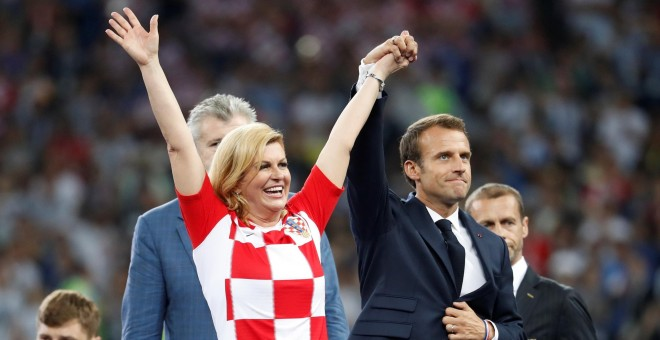 Emmanuel Macron levanta la mano de la presidenta de Croacia Kolinda Grabar-Kitarovic. REUTERS